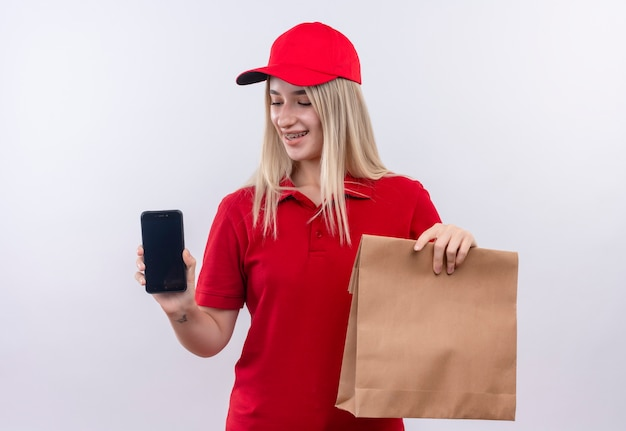 Lächelndes junges mädchen der lieferung, das rotes t-shirt und kappe in der zahnspange trägt, die telefon und papiertasche auf lokalisiertem weißem hintergrund hält