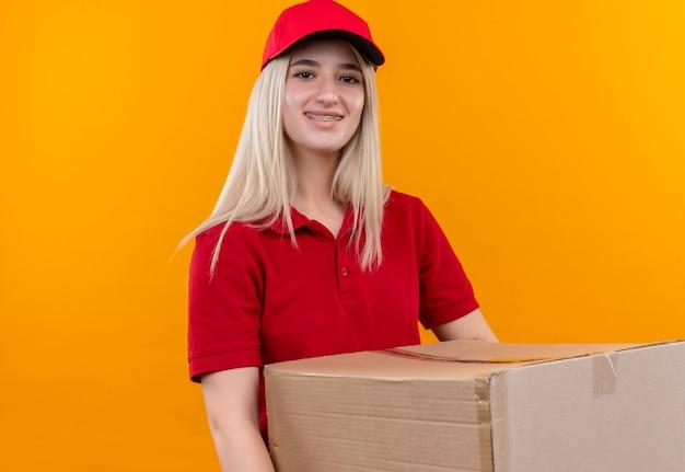 Lächelndes junges mädchen der lieferung, das rotes t-shirt und kappe in der zahnspangenhaltebox auf lokalem orange hintergrund trägt