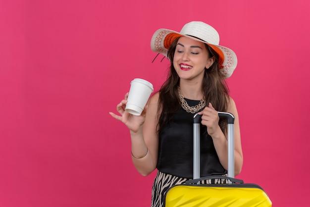 Lächelndes junges mädchen des reisenden, das schwarzes unterhemd im hut hält, der koffer hält und tasse kaffee auf rotem hintergrund betrachtet