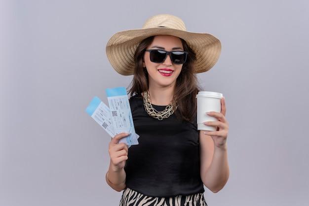 Lächelndes junges mädchen des reisenden, das schwarzes unterhemd im hut trägt, das brillen trägt, die tickets und tasse kaffee auf weißem hintergrund halten