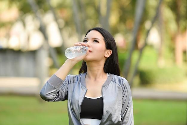 Lächelndes junges mädchen des trinkwasserflaschen-gesundheitskonzeptes der frau entspannen sich