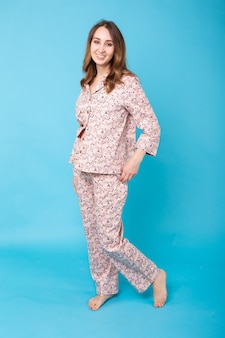 Lächelndes junges mädchen im schlafanzug-haus tragen, das posiert, während zu hause isoliert auf blauer wand ruht