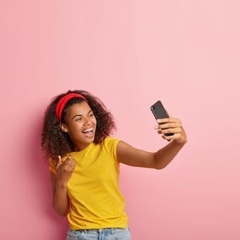 Lächelndes junges mädchen mit dem gelockten haar, das im gelben t-shirt aufwirft