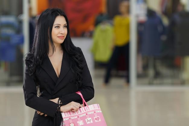 Lächelndes junges mädchen mit einkaufstüten schaut im einkaufszentrum von der kamera weg