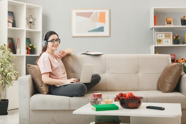 Lächelndes junges mädchen mit laptop mit kopfhörern und brille sitzt auf dem sofa hinter dem couchtisch im wohnzimmer