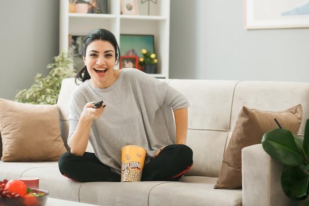 Lächelndes junges mädchen mit popcorn-eimer, das die tv-fernbedienung hält und auf dem sofa hinter dem couchtisch im wohnzimmer sitzt
