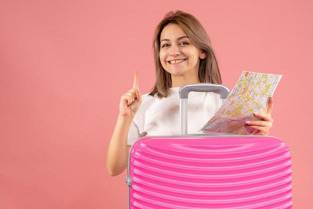 Lächelndes junges mädchen mit rosa koffer mit karte, die mit dem finger nach oben zeigt