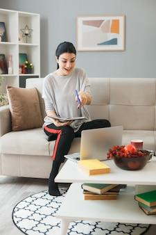 Lächelndes junges mädchen verwendet und zeigt auf laptop mit notebook, das auf dem sofa hinter dem couchtisch im wohnzimmer sitzt
