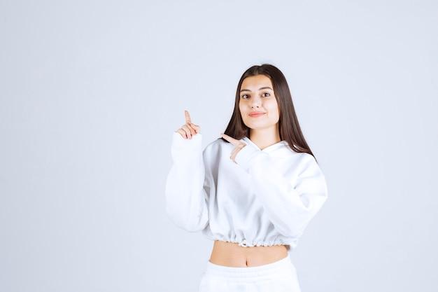 Lächelndes junges mädchenmodell, das mit den zeigefingern nach oben zeigt.
