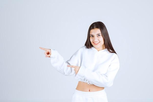 Lächelndes junges mädchenmodell, das mit den zeigefingern weg zeigt.