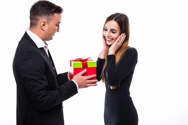 Lächelndes junges mann- und mädchenpaar präsentieren geschenk in der roten schachtel auf weiß
