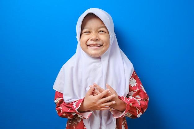 Lächelndes junges muslimisches mädchen in roter kleidung des hijab, kamera lokalisiert auf blauem wandhintergrund, studioporträt suchend. menschen religiöses lifestyle-konzept. Premium Fotos