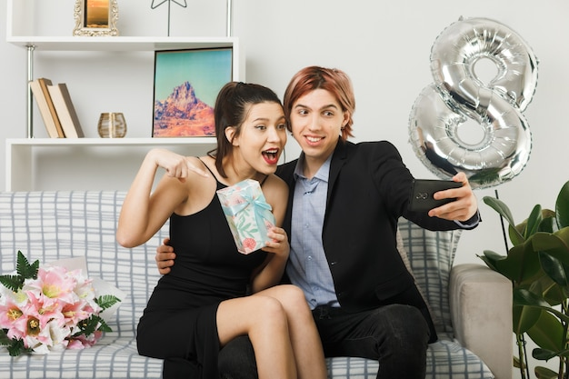 Lächelndes junges paar am glücklichen frauentag, das derzeit hält und punkte macht, macht ein selfie, das auf dem sofa im wohnzimmer sitzt