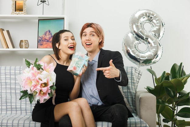 Lächelndes junges paar am glücklichen frauentag hält und zeigt auf blumenstrauß und gegenwart, die auf dem sofa im wohnzimmer sitzt