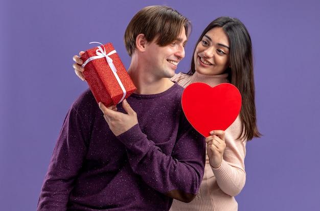 Lächelndes junges paar am valentinstag, das sich anschaut und eine herzförmige schachtel mit geschenkbox auf blauem hintergrund hält