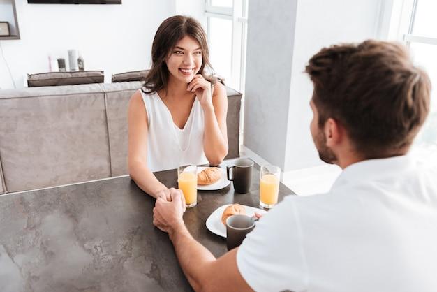 Lächelndes junges paar beim frühstück und händchenhalten zu hause