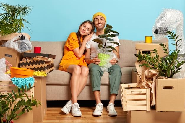 Lächelndes junges paar, das auf der couch sitzt, umgeben von kisten