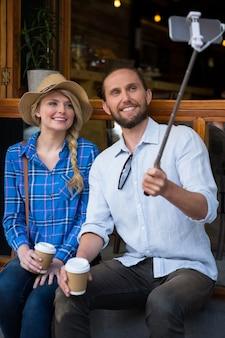 Lächelndes junges paar, das durch selfie-stock im kaffeehaus fotografiert