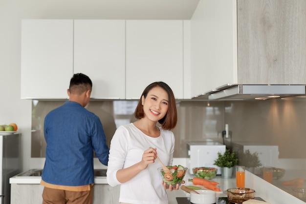 Lächelndes junges paar, das essen in der küche kocht