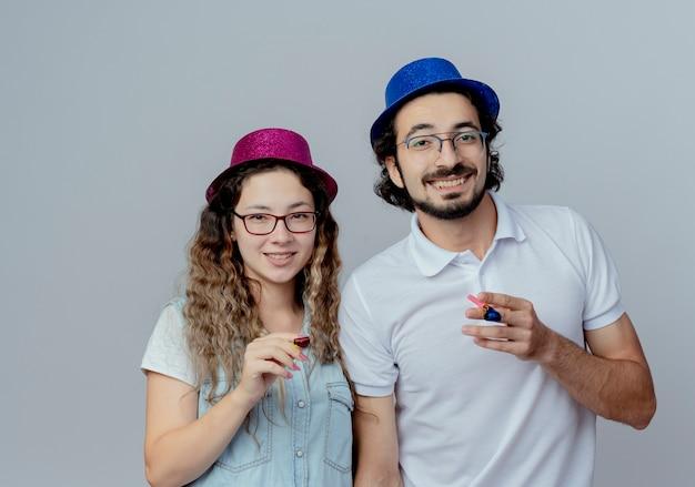 Lächelndes junges paar, das geburtstagshüte trägt, die pfeife lokalisiert auf weiß halten