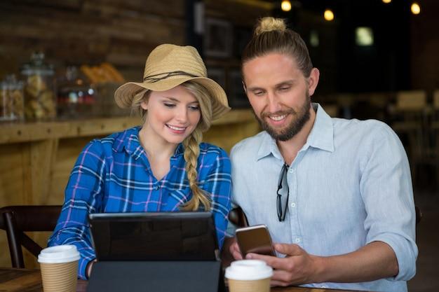 Lächelndes junges paar, das handy am tisch im café benutzt