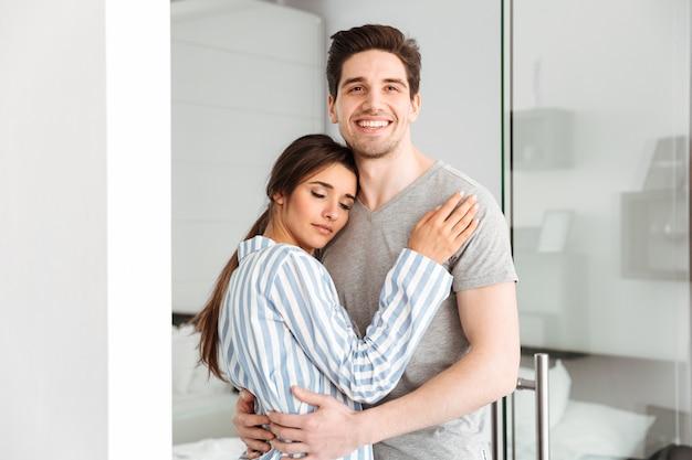 Lächelndes junges paar, das im stehen umarmt