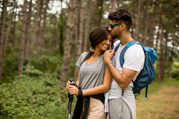 Lächelndes junges paar, das mit rucksäcken im wald an einem sommertag geht