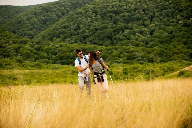 Lächelndes junges paar, das mit rucksäcken über grünen hügeln geht