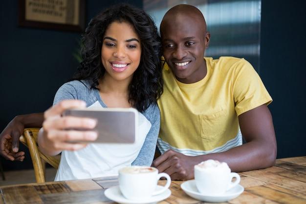 Lächelndes junges paar, das selfie mit handy im kaffeehaus nimmt