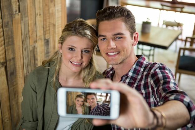 Lächelndes junges paar, das selfie mit handy in der cafeteria nimmt