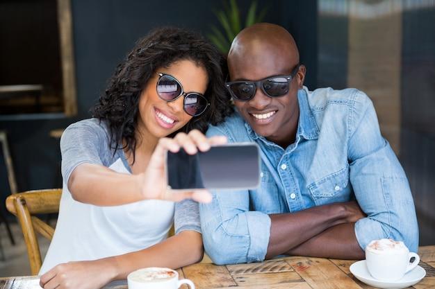 Lächelndes junges paar, das selfie mit smartphone im kaffeehaus nimmt