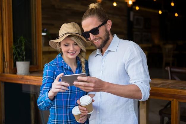 Lächelndes junges paar, das smartphone im coffeeshop verwendet