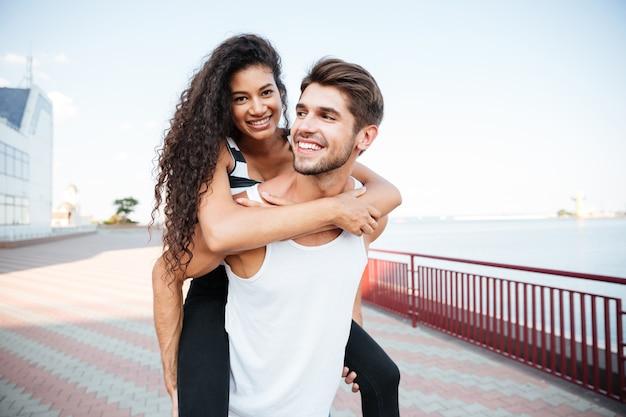 Lächelndes junges paar, das spazieren geht und spaß hat