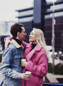 Lächelndes junges paar in der stadt, die kaffee trinkt.