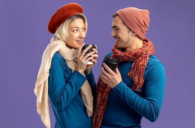 Lächelndes junges paar mit hut mit schal am valentinstag, das sich anschaut und eine tasse kaffee isoliert auf blauem hintergrund hält