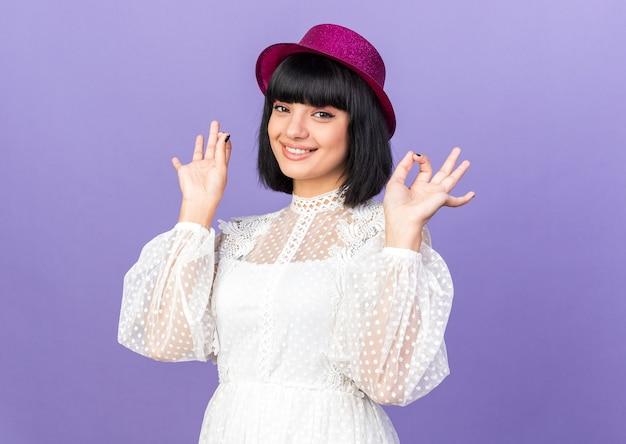Lächelndes junges partygirl mit partyhut, das ein gutes zeichen auf lila wand isoliert tut