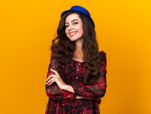 Lächelndes junges partygirl mit partyhut, das mit geschlossener haltung isoliert auf oranger wand mit kopierraum steht