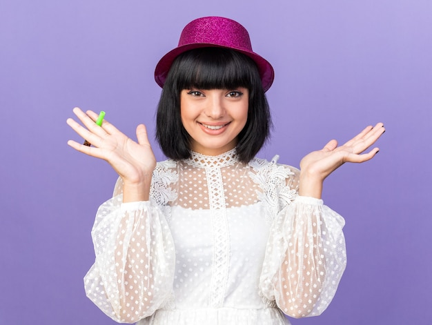 Lächelndes junges partygirl mit partyhut, das partyhorn hält und nach vorne schaut und leere hand isoliert auf lila wand zeigt Premium Fotos