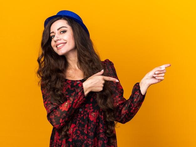 Lächelndes junges partygirl mit partyhut, der auf die seite zeigt, die auf orangefarbener wand isoliert ist?