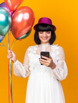 Lächelndes junges partymädchen mit partyhut, das luftballons hält und das handy auf oranger wand isoliert anschaut