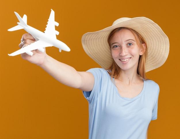 Lächelndes junges rothaariges ingwermädchen mit sommersprossen, das strandhut trägt, hält modellflugzeug isoliert auf oranger wand mit kopierraum