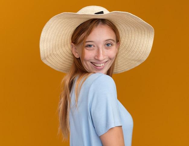 Lächelndes junges rothaariges ingwermädchen mit sommersprossen, die strandhut tragen, der seitlich auf orange steht