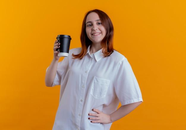 Lächelndes junges rothaariges mädchen, das tasse kaffee hält und hand auf hüfte lokalisiert auf gelbem hintergrund setzt
