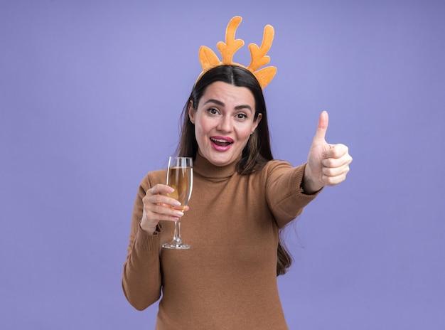 Lächelndes junges schönes mädchen, das braunen pullover mit weihnachtshaarbügel hält, der glas champagner zeigt daumen oben auf blauem hintergrund