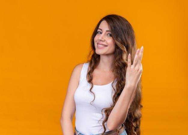 Lächelndes junges schönes mädchen, das drei auf lokalisiertem orange raum mit kopienraum zeigt