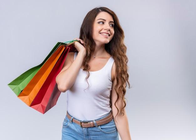 Lächelndes junges schönes mädchen, das einkaufstaschen auf schulter hält, die rechte seite mit kopienraum betrachtet