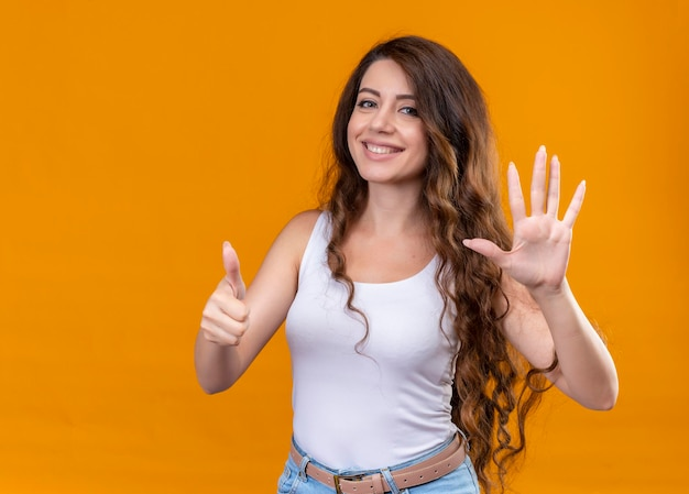 Lächelndes junges schönes mädchen, das fünf und daumen oben auf lokalisiertem orange raum mit kopienraum zeigt