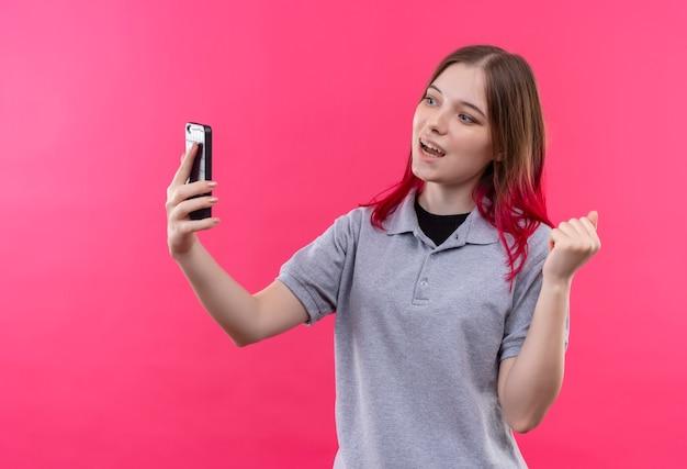 Lächelndes junges schönes mädchen, das graues t-shirt trägt, das telefon in ihrer hand betrachtet, die ja geste auf lokalisiertem rosa hintergrund zeigt