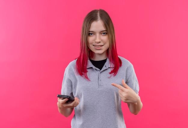 Lächelndes junges schönes mädchen, das graues t-shirt trägt, zeigt finger auf telefon in ihrer hand auf lokalisiertem rosa hintergrund mit kopienraum