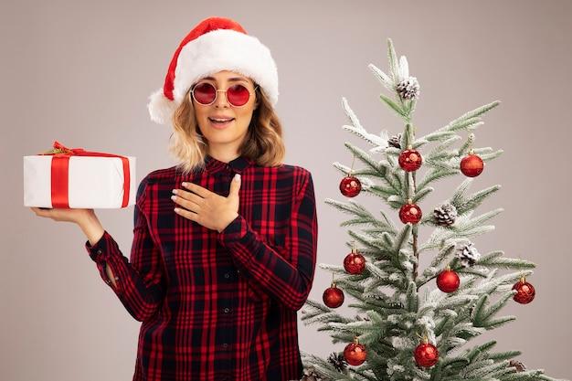 Lächelndes junges schönes mädchen, das in der nähe des weihnachtsbaums steht und eine weihnachtsmütze mit brille hält, die eine geschenkbox hält, die sich die hand auf sich selbst legt, isoliert auf weißem hintergrund